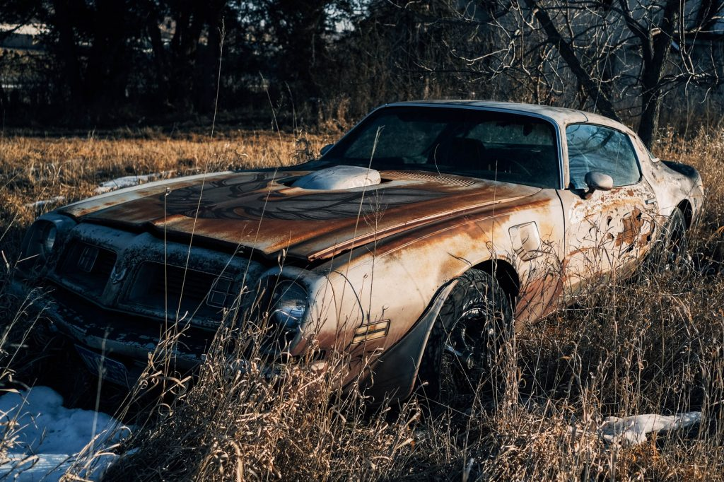 An abandoned Trans Am in next to an old house and tree, found in Iowa.