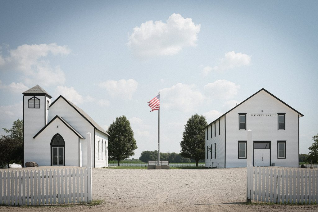A photograph of a community hall and church in Elk City, Nebraska. Shot with an Fuji X-E4 and XF 27mm f/2.8.